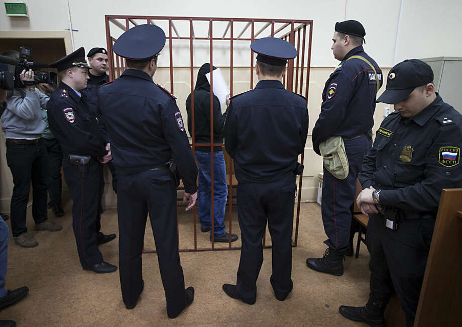 Police surround a cage with Khamzad Bakhaev, one of five suspects in the killing of Russian opposition politician Boris Nemtsov, in a court in Moscow, Russia, Monday, April 6, 2015. Investigators have detained five men in connection to Nemtsov's killing, all of them from Chechnya or other parts of Russia's predominantly Muslim North Caucasus. Prime suspects Zaur Dadaev and Anzor Gubashev were charged in connection to the shooting. A judge said Dadaev had confessed to investigators, though he did not admit guilt in court. The three others, who included Gubashev's younger brother Shagid, Khamzad Bakhaev and Tamerlan Eskerkhanov, have been detained but not charged. (AP Photo/Ivan Sekretarev)