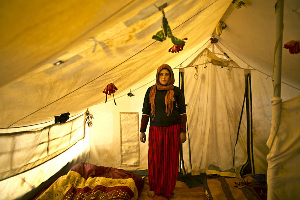 In this Monday, March 16, 2015 photo, pregnant Syrian refugee Wadhah Hamada, 22, poses for a portrait inside her tent at an informal settlement near the Syrian border, on the outskirts of Mafraq, Jordan. Hamada, who fled al-Hasaka, Syria, says she has no clue how her four-month pregnancy is progressing.