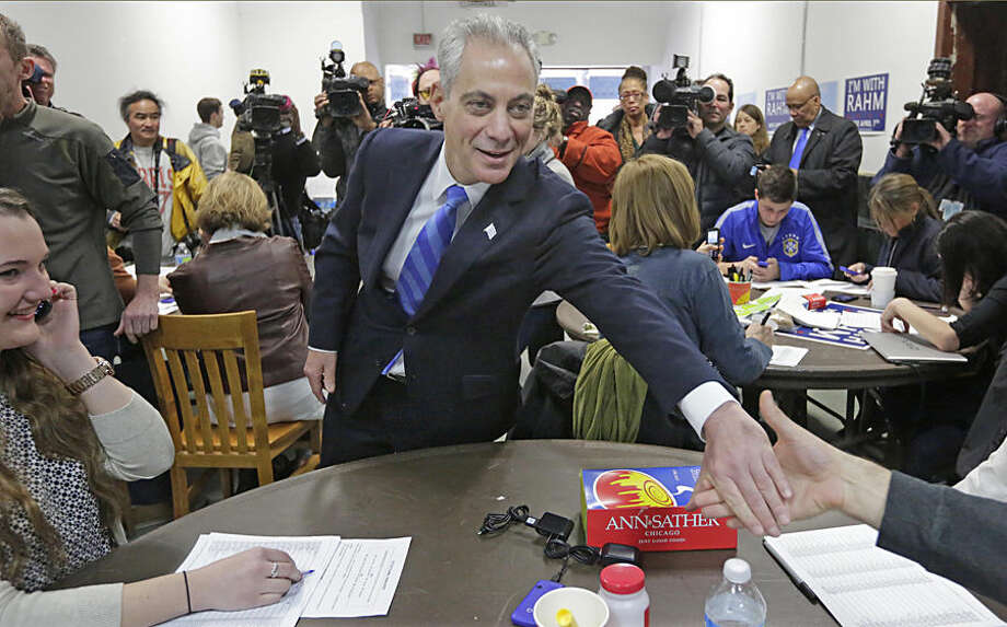 "Mayor Rahm Emanuel shakes hands at a campaign office, Monday, April 6, 2015, in Chicago, as he and his opponent, Cook County Commissioner Jesus ""Chuy"" Garcia, rally supporters ahead of the city's mayoral runoff election on Tuesday. It's the first runoff since Chicago switched to non-partisan elections 20 years ago. (AP Photo/M. Spencer Green)"