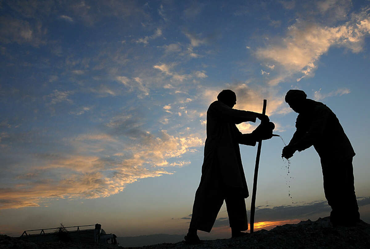 An Afghan farmer, left, pours water for his colleague to wash his hand after finishing work in Mazar-i Sharif, capital of Balkh, north of Kabul, Afghanistan on Monday, April 6, 2015. (AP Photo/Mustafa Najafizada)