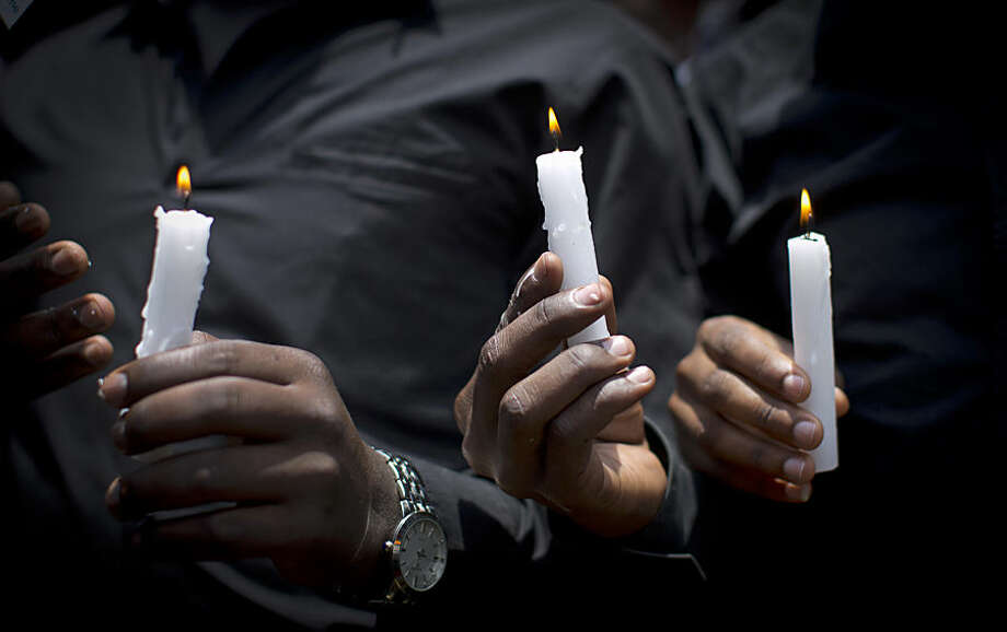 Kenyan students wearing black shirts to represent mourning hold candles as they march in memory of the victims of the Garissa college attack and to protest what they say is a lack of security, in downtown Nairobi, Kenya Tuesday, April 7, 2015. Hundreds of Kenyan students marched through downtown Nairobi on Tuesday to honor those who died in the attack on a college by Islamic militants and to press the government for better security in the wake of the slaughter. (AP Photo/Ben Curtis)