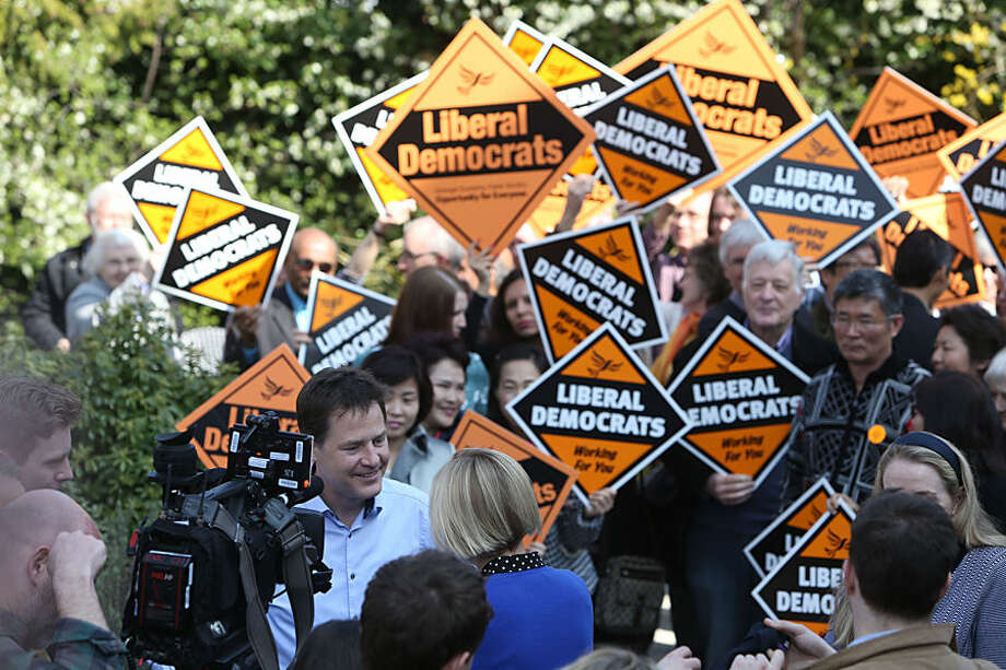 Britain's Liberal Democrat Party leader Nick Clegg, facing camera centre left, speaks to the media while being surrounded by supporter outside the Grove Pub, while on the General Election campaign trail in Surbiton, London. Monday April 6, 2015. Britain goes to the polls in a parliamentary election on Thursday May 7, 2015. (AP Photo/Steve Parsons/PA) UNITED KINGDOM OUT - NO SALES - NO ARCHIVE