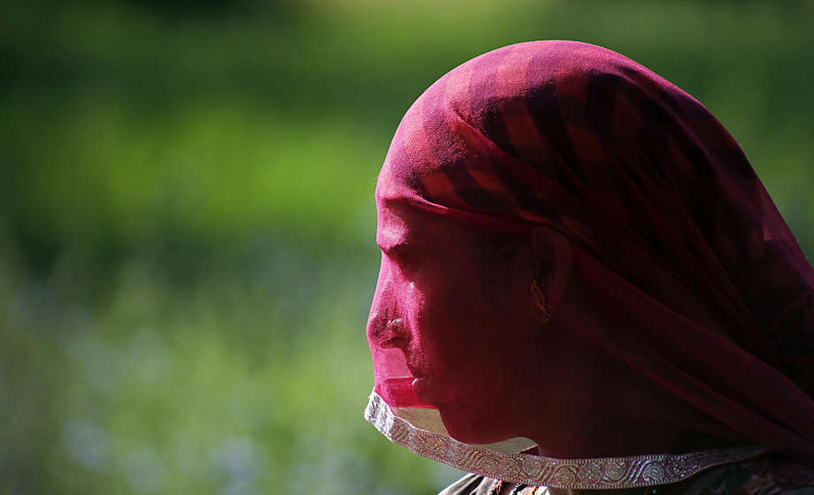 An Indian farmer stands in a field as she harvests wheat crop that was partially damaged in unseasonal hailstorm and rain, on the outskirt of Ajmer, India, Tuesday, April 7, 2015. Unseasonal rainfall over large parts of northwest and central India caused widespread damage to standing crops. (AP Photo/Deepak Sharma)
