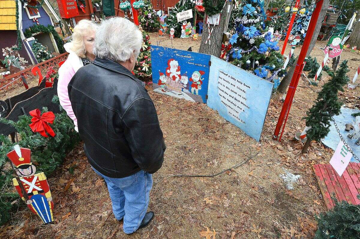 Hour Photo/Alex von Kleydorff Rick and Joan Setti will hold a tag sale to sell the items they have built and displayed over the last 26 Holiday's at their Norwalk home.They pause to read a greeting card with their message to all who have passed through the display