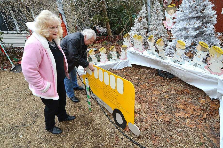 Hour Photo/Alex von Kleydorff Rick and Joan Setti will hold a tag sale to sell the items they have built and displayed over the last 26 Holiday's at their Norwalk home. Here they straighten a school bus full of angels that will be donated to Sandy Hook