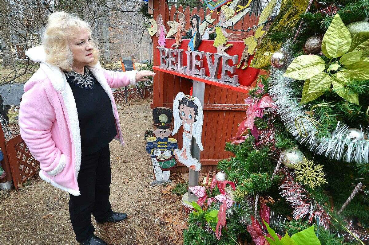 Hour Photo/Alex von Kleydorff Rick and Joan Setti will hold a tag sale to sell the items they have built and displayed over the last 26 Holiday's at their Norwalk home.They take a walk through the display and Joan stops at an angel and a believe sign near one of the many Christmas trees used