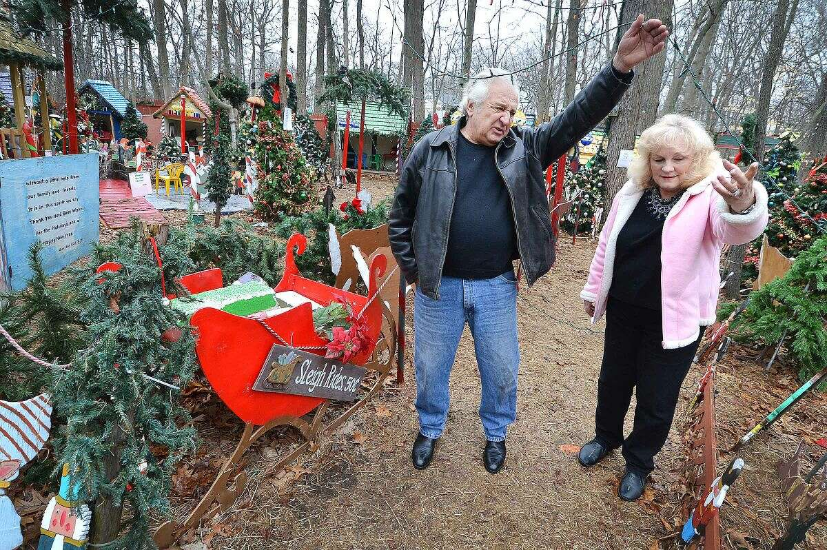 Hour Photo/Alex von Kleydorff Rick holds up a string of lights so his wife Joan can pass under, during a walk through of their Christmas display on Tuesday. Rick and Joan Setti will hold a tag sale to sell the items they have built and displayed over the last 26 Holiday's at their Norwalk home