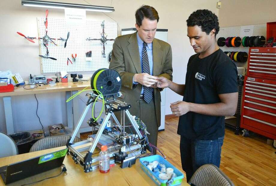 Hour Photo/Alex von Kleydorff Fairfield County Makers Guild founding member Vladimir Mariano shows Jim Himes some of the tasks the 3D printer can accomplish