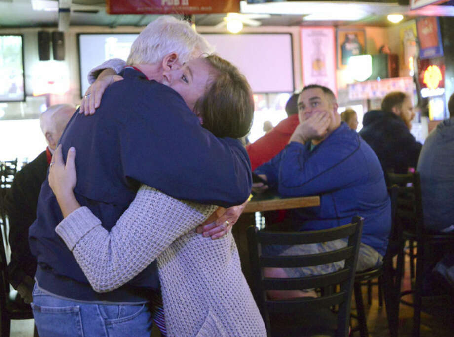 Pub II waitress Maddie DeGaealu and long time customer and friend Ken Hoffacker embrace while comforting each other in the Normal, Ill., bar, after learning that co-owner Terry Stralow is one of seven killed in the crash of a small aircraft east of Bloomington, Ill., Tuesday, April 7, 2015. (AP Photo/The Pantagraph, Steve Smedley)