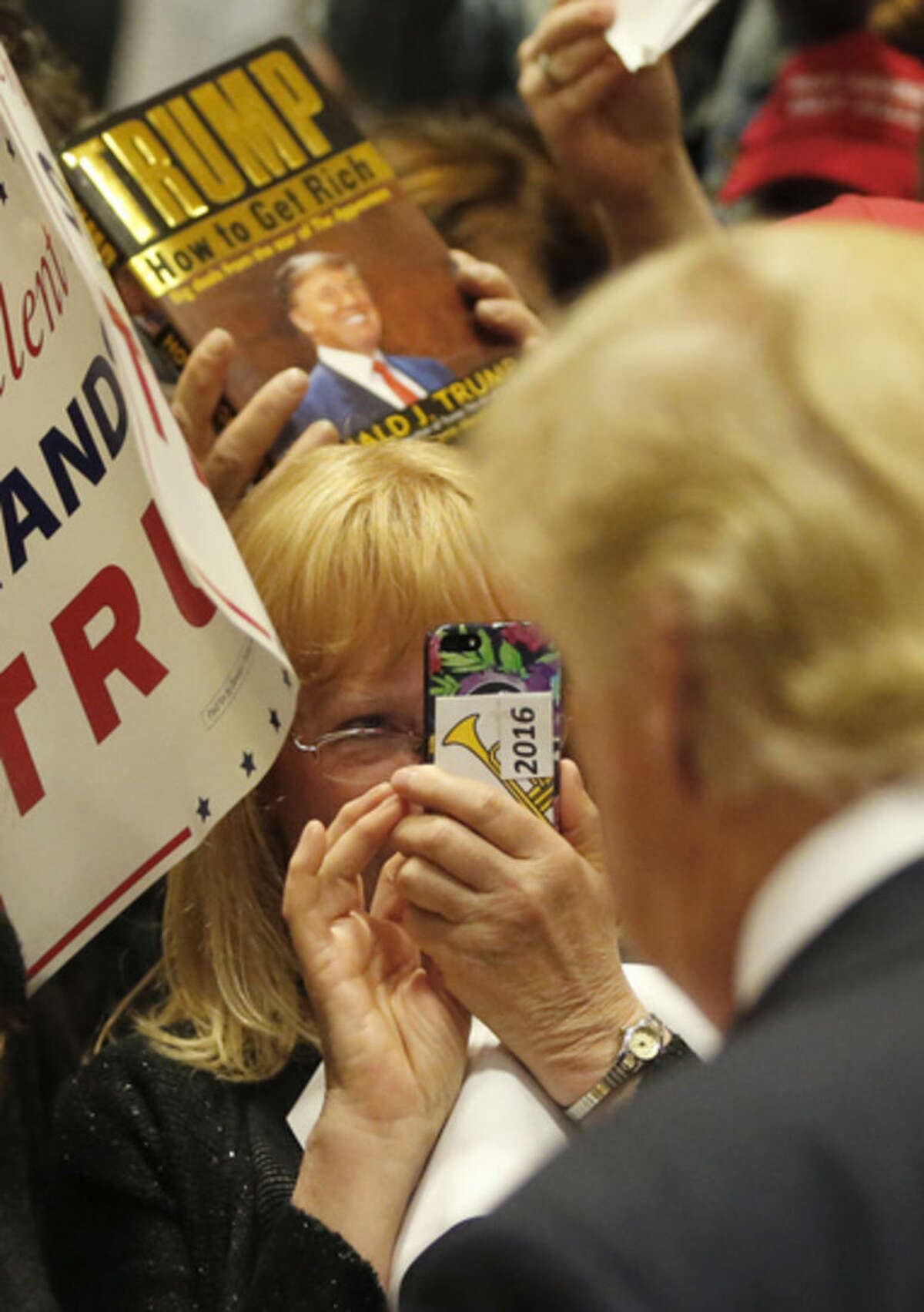 A supporter of Republican presidential candidate, Donald Trump, takes his photograph after a rally at Nathan Hale High School, Sunday, April 3, 2016, in West Allis, Wis. (AP Photo/Charles Rex Arbogast)