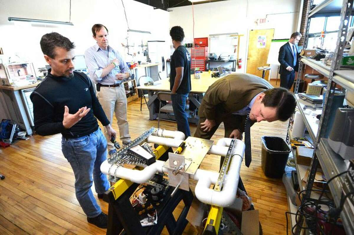 Hour Photo/Alex von Kleydorff Makers Guild Founder Brian Davis shows Jim Himes his latest project, an autonomous robot being fabricated in the Fairfield County Makers Space studio