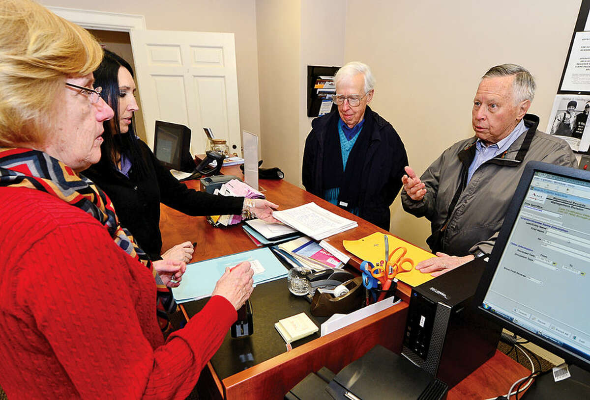 Hour photo / Erik Trautmann Sensible Wilton members Curt Noel and Alex Ruskewich, on right, submit a petition challenging a renovation budget for Miller -Driscoll School to the Town Clerk's office while clerks Lori Kaback and Ann Fiteni look on.