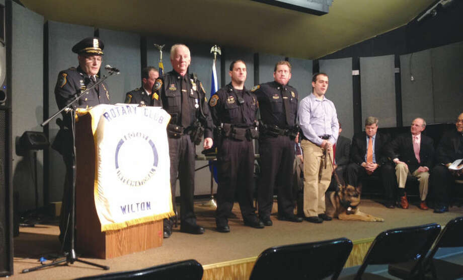 Pictured at the ceremony, from left to right are: Police Chief Michael Lombardo, Sgt. Thomas Tunney, Officer Tim Fridinger, Officer Michael Tyler, Officer Frank Razzaia, Canine Squad member Enzo; and seated are: police commissioners Chris Weldon and Donald Sauvigne. Capt. John Lynch is shown in the background.