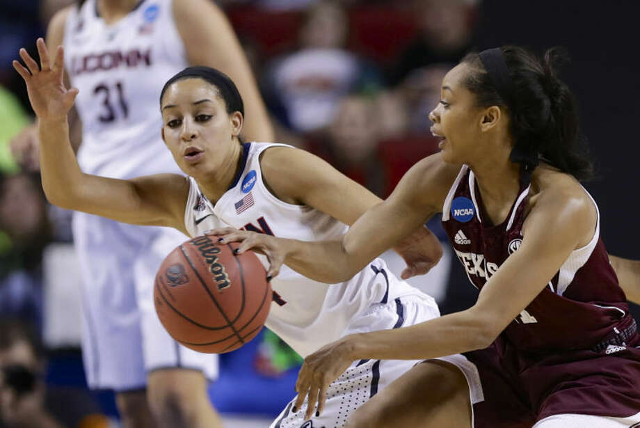 Texas A&M's Curtyce Knox, right, passes the ball past Connecticut's Bria Hartley, left, during the first half of a regional final game in the NCAA college basketball tournament in Lincoln, Neb., Monday, March 31, 2014. (AP Photo/Nati Harnik)