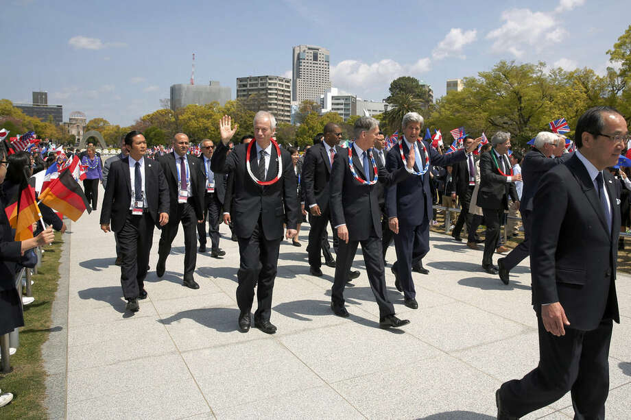 Canada's Foreign Minister Stephane Dion, waving at center, Britain's Foreign Minister Philip Hammond, second right, and U.S. Secretary of State John Kerry, right, wave to schoolchildren as they and fellow G7 foreign ministers visit the Hiroshima Peace Memorial Park in Hiroshima, western Japan Monday, April 11, 2016. (Jonathan Ernst/Pool Photo via AP)