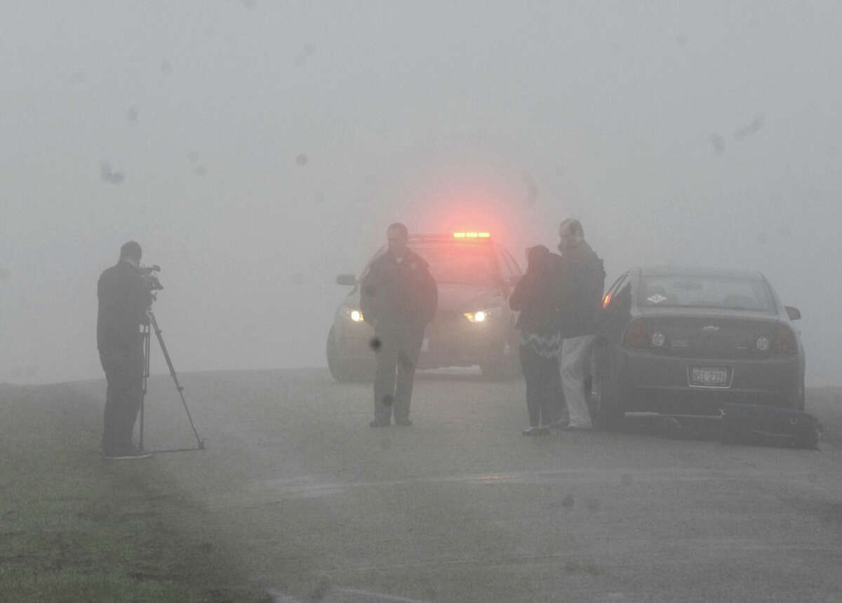 Emergency personnel and media gather at the scene near Bloomington, Ill., where a small plane, with at least five on board, crashed early Tuesday, April 7, 2015. The Federal Aviation Administration says the Cessna 414 crashed just short of the Bloomington airport after midnight Tuesday while returning from the NCAA basketball championship in Indianapolis. (AP Photo/The Pantagraph, David Proeber)