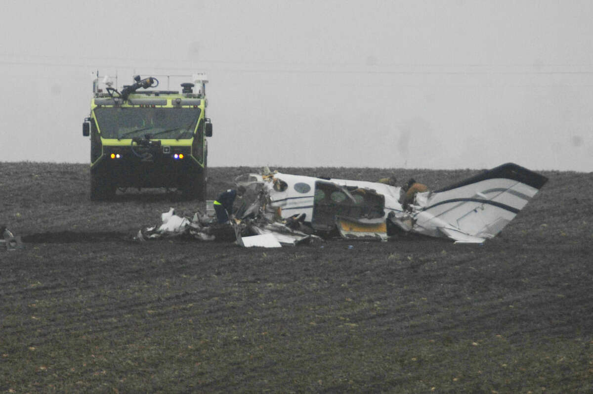 Investigators work at the site of a small plane crash near Bloomington, Ill., Tuesday, April 7, 2015, that claimed the lives of seven people. The Cessna 414 took off from Indianapolis and crashed just short of the Central Illinois Regional Airport in Bloomington after midnight. The plane was returning from the NCAA Final Four tournament in Indianapolis. (AP Photo/The Pantagraph, David Proeber)
