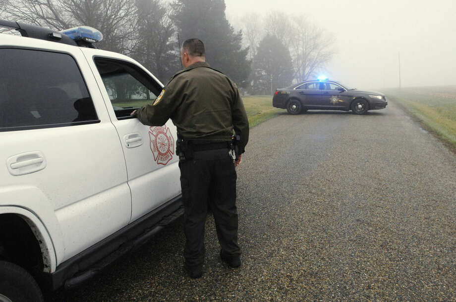 A McLean County sheriff's deputy mans a roadblock at the scene near Bloomington, Ill., where a small plane crashed with at least five on board crashed early Tuesday, April 7, 2015. The Federal Aviation Administration says the Cessna 414 crashed just short of the Bloomington airport after midnight Tuesday while returning from the NCAA basketball championship in Indianapolis. (AP Photo/The Pantagraph, David Proeber)