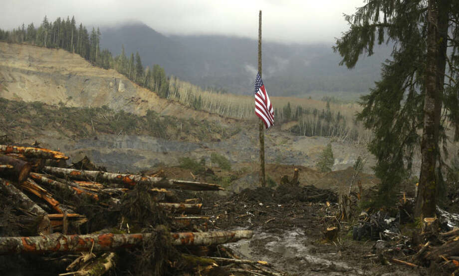 A flag flies at half-staff on a log Sunday, March 30, 2014, with the slope of the massive mudslide that struck Saturday, March 22, 2014 in the background. The search for victims of the deadly slide continued Sunday, with crews searching both with heavy machinery and by hand. (AP Photo/Ted S. Warren)