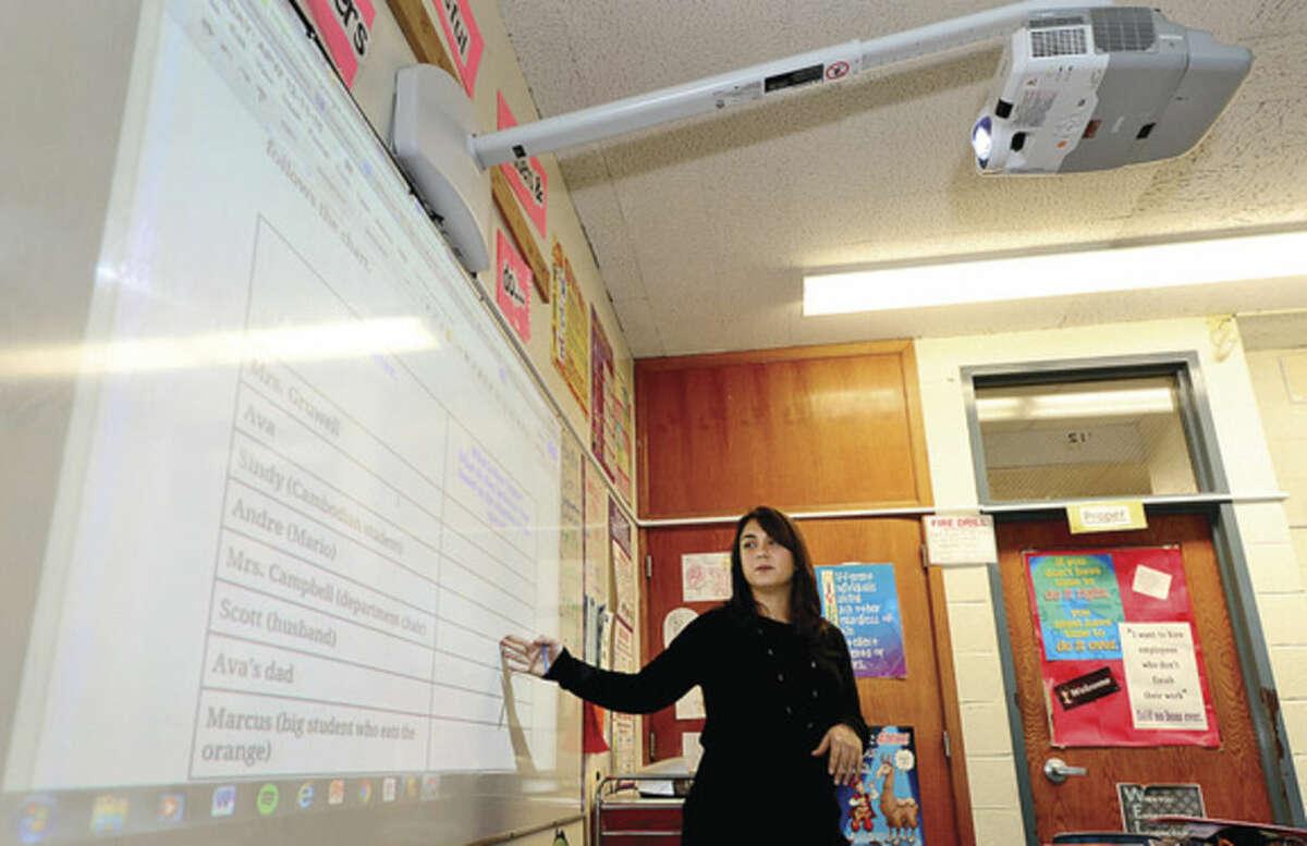 Hour photo / Erik Trautmann Ponus Ridge Middle School teacher Ashley Bonora instructs her 8th graders during her paperless Language Arts class Thursday.