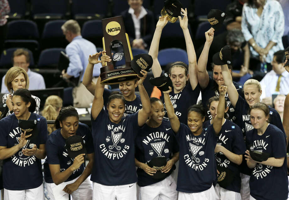 Connecticutplayers pose with the national championship trophy after the NCAA women's Final Four tournament college basketball championship game against Notre Dame, Tuesday, April 7, 2015, in Tampa, Fla. Connecticut won 63-53. (AP Photo/Chris O'Meara)