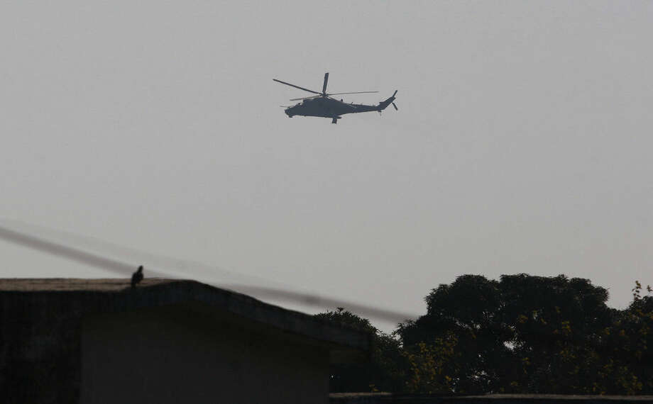 An Indian air force chopper on a reconnaissance mission flies over the Indian airbase in Pathankot, 430 kilometers (267 miles) north of New Delhi, India, Saturday, Jan. 2, 2016. At least four gunmen entered an Indian air force base near the border with Pakistan on Saturday morning and exchanged fire with security forces, leaving two of them dead, officials said. (AP Photo/Channi Anand)