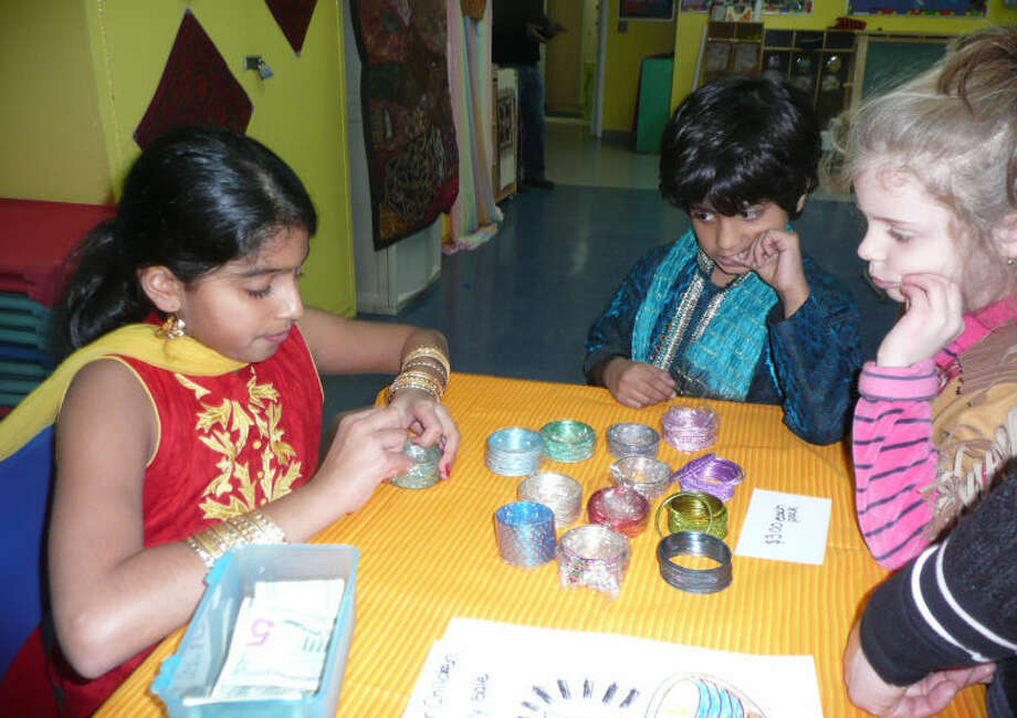 Young attendees are pictured admiring colorful bracelets offered at a booth during the previous Indian Festival hosted by the Wilton Family Y.
