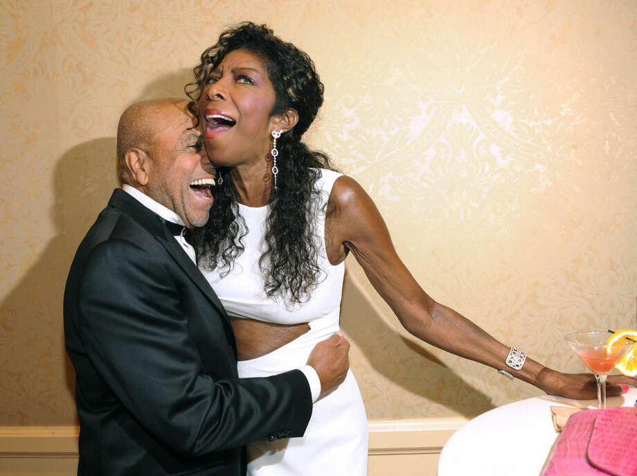 """FILE - In a Saturday, Oct. 11, 2014 file photo, Motown Records founder Berry Gordy, left, embraces singer Natalie Cole at the 2014 Carousel of Hope Ball at the Beverly Hilton Hotel, in Beverly Hills, Calif. Cole, the daughter of jazz legend Nat """"King"""" Cole who carried on his musical legacy, died Thursday night, Dec. 31, 2015, according to publicist Maureen O'Connor. She was 65. (Photo by Chris Pizzello/Invision/AP, File)"""