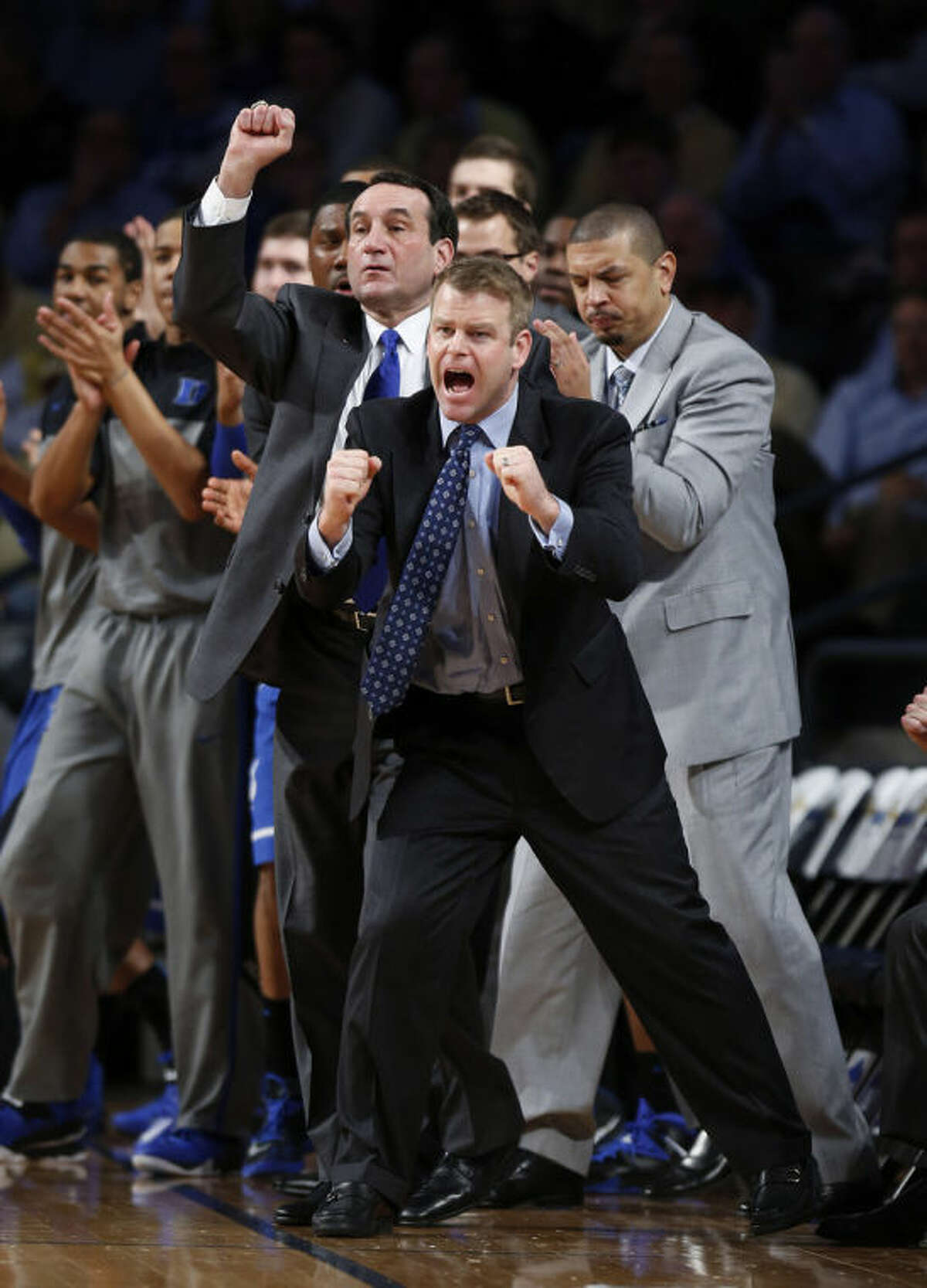 FILE - In this Feb. 18, 2014, file photo, Duke assistant coach Steve Wojciechowski, foreground, head coach Mike Krzyzewski, second from left, react during the first half of a basketball game against Georgia Tech in Atlanta. A person familiar with the situation says Marquette has hired Duke assistant Wojciechowski as its next men's basketball coach. The person spoke to The Associated Press Tuesday, April 1, on condition of anonymity because Marquette has not announced Wojciechowski's hiring. (AP Photo/John Bazemore, File)