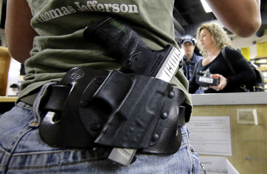Kayla Brown, left, wears her gun on her hip while working at the Spring Guns and Amo store Monday, Jan. 4, 2016, in Spring, Texas. President Barack Obama defended his plans to tighten the nation's gun-control restrictions on his own, insisting Monday that the steps he'll announce fall within his legal authority and uphold the constitutional right to own a gun. (AP Photo/David J. Phillip)
