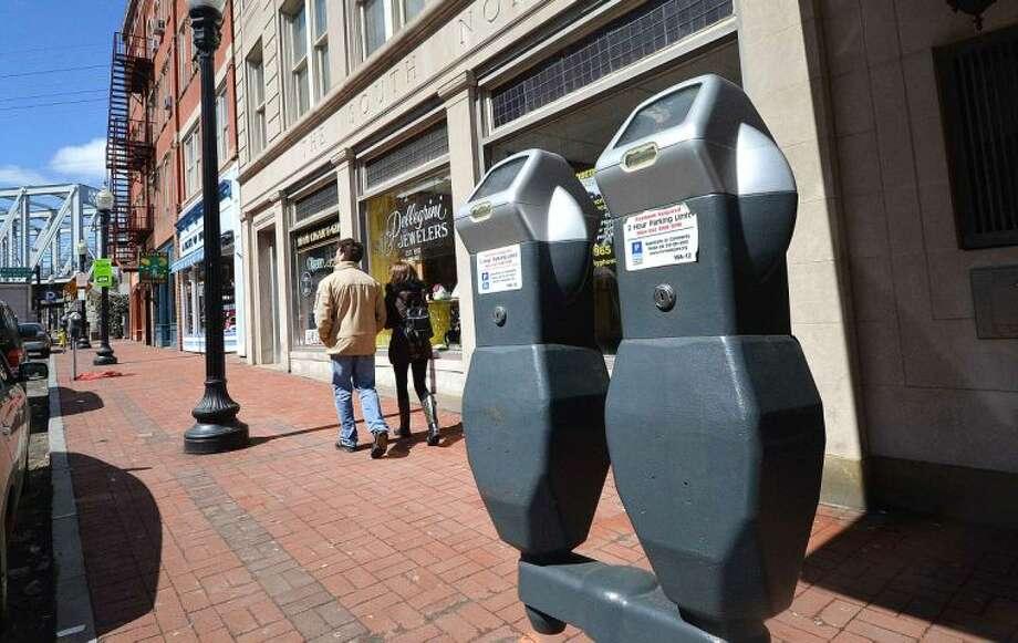 Hour Photo/Alex von Kleydorff. People walk on Washington St. past Parking Meters in SONO on Monday