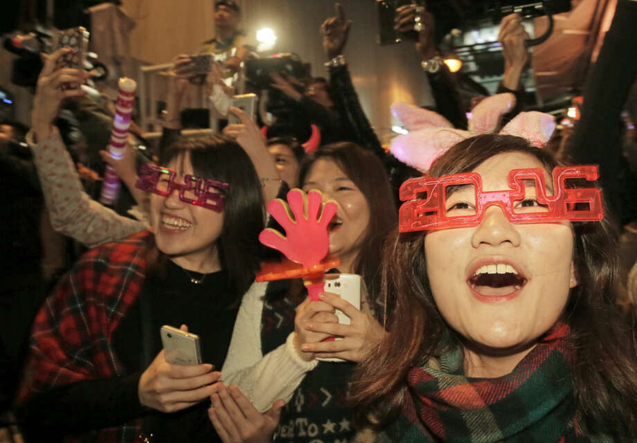 Revellers smile during the New Year's Eve celebrations in Hong Kong's Lan Kwai Fong, Friday, Jan. 1, 2016. (AP Photo/Vincent Yu)