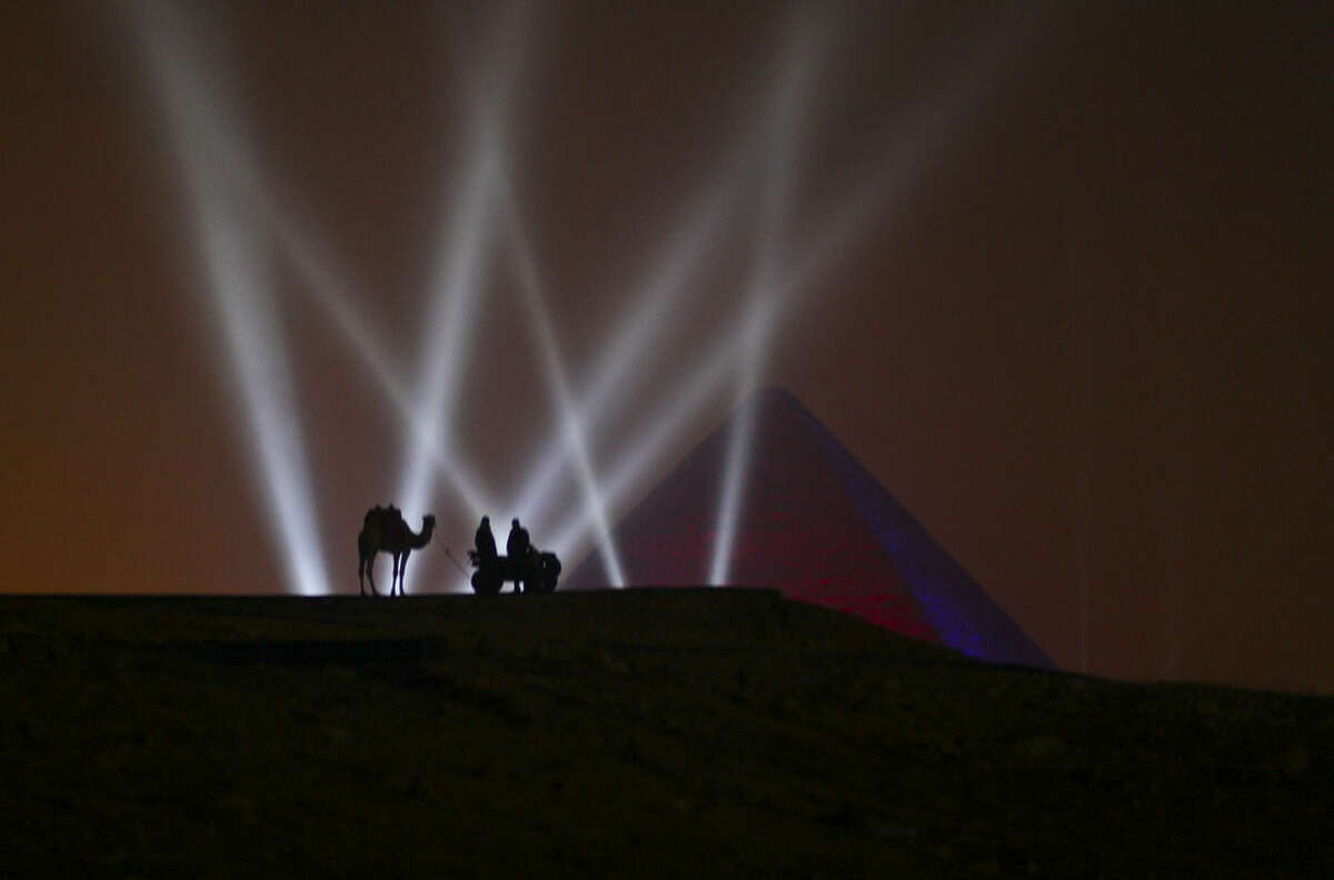 Two Egyptian men and a camel stand on a hill overlooking one of the Giza Pyramids during a New Year's Eve fireworks display near Cairo, Egypt at midnight on Friday, Jan. 1, 2016. (AP Photo/Maya Alleruzzo)