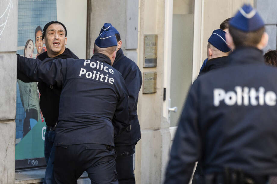 Police officers detain a man in the historic center in Brussels on Thursday, Dec. 31, 2015. The New Year's Eve fireworks display and all official events are being canceled in Belgium's capital due to threats of an extremist attack. It was not known why the man was detained. (AP Photo/Geert Vanden Wijngaert)