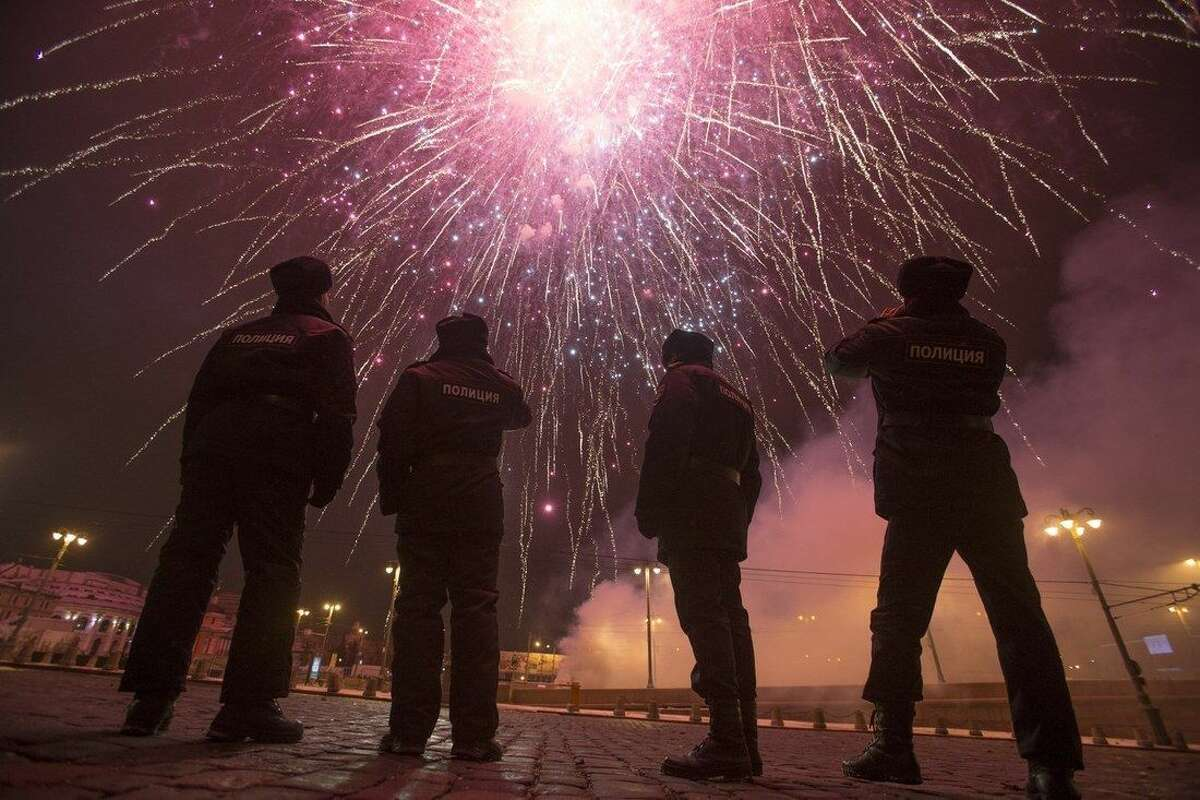 Police officers photograph fireworks as they guard Red Square in Moscow, Russia, in Moscow, Russia, Friday, Jan. 1, 2016. Putin is using his New Year's message to commemorate both the country's current fight in Syria and the battles of World War II seven decades ago. The recorded message was being televised just before midnight Thursday in each of Russia's nine time zones. (AP Photo/Denis Tyrin)