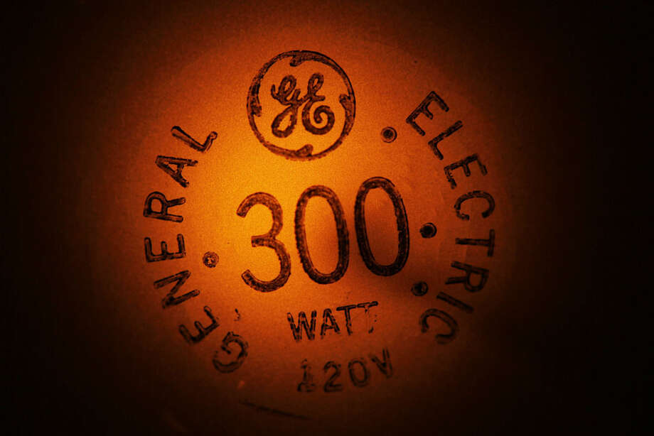 In this photo taken Jan. 14, 2011, a General Electric light bulb glows as it is turned off in Buffalo, N.Y. General Electric Co. (GE) on Friday April 17, 2015 reported a first-quarter loss of $13.57 billion, after reporting a profit in the same period a year earlier. (AP Photo/David Duprey, File)