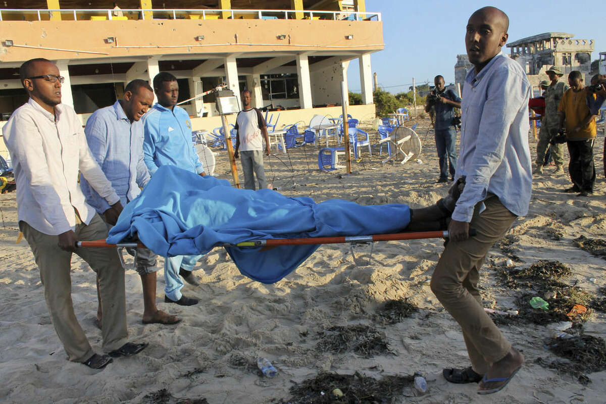 Relatives carry away a dead body from the beach following an overnight attack on a beachfront restaurant in Mogadishu, Somalia, Friday, Jan. 22, 2016. Somalia's security forces ended a deadly siege of a beachfront restaurant in the capital, with many killed in the attack, a police official said Friday. (AP Photo/Farah Abdi Warsameh)