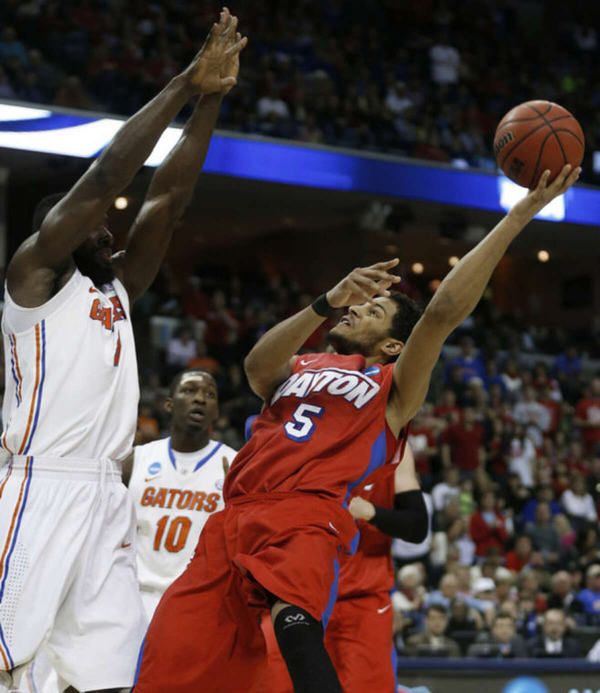Dayton forward Devin Oliver (5) shoots against Florida center Patric Young (4) during the first half in a regional final game at the NCAA college basketball tournament, Saturday, March 29, 2014, in Memphis, Tenn. (AP Photo/John Bazemore)
