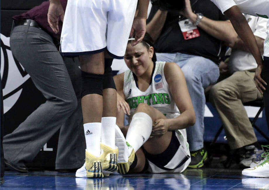 Notre Dame forward Natalie Achonwa is tended to by a trainer in the second half of their NCAA women's college basketball tournament regional final game against Baylor at the Purcell Pavilion in South Bend, Ind., Monday, March 31, 2014. Achonwa left the game with the injury. (AP Photo/Paul Sancya)