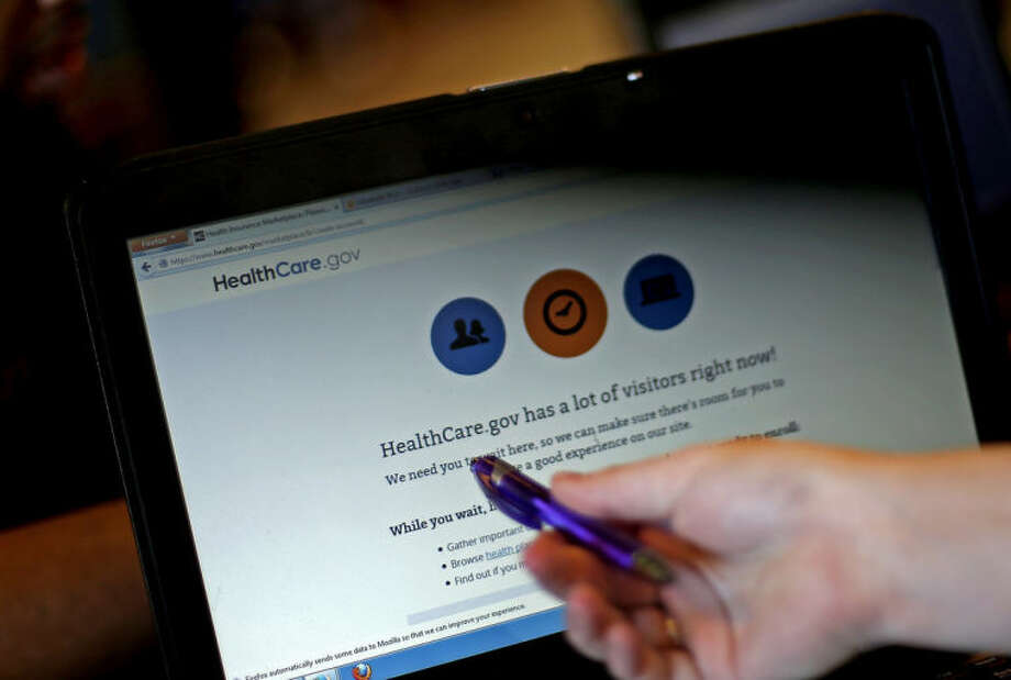 Elizabeth Rich points to a web page for the Affordable Care Act as she helps people sign up for health insurance at Swope Health Services Monday, March 31, 2014, in Kansas City, Mo. Today is the deadline to sign up for an Affordable Health Care insurance plan however, people who begin the enrollment process but aren't able to complete it by 11:59 p.m. because of a system issue may qualify for a special provision that will allow them to enroll after Monday night. (AP Photo/Charlie Riedel)