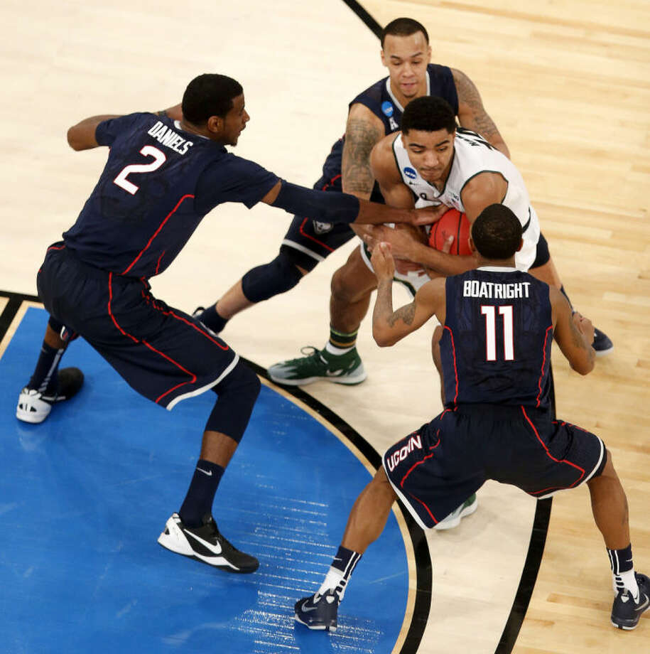 Michigan State guard Gary Harris, center, fights off Connecticut forward DeAndre Daniels (2), guard Ryan Boatright (11) and guard Shabazz Napier during the second half in a regional semifinal at the NCAA college basketball tournament on Sunday, March 30, 2014, in New York. (AP Photo/Julio Cortez)