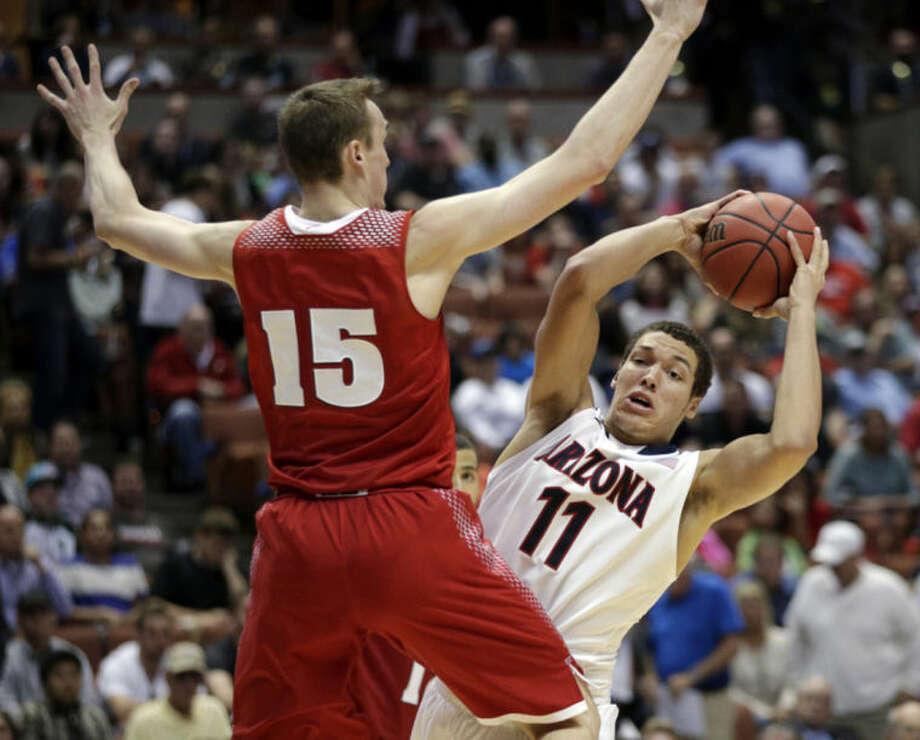 Wisconsin 's Sam Dekker (15) defends Arizona's Aaron Gordon (11) during the second half in a regional final NCAA college basketball tournament game, Saturday, March 29, 2014, in Anaheim, Calif. (AP Photo/Jae C. Hong)