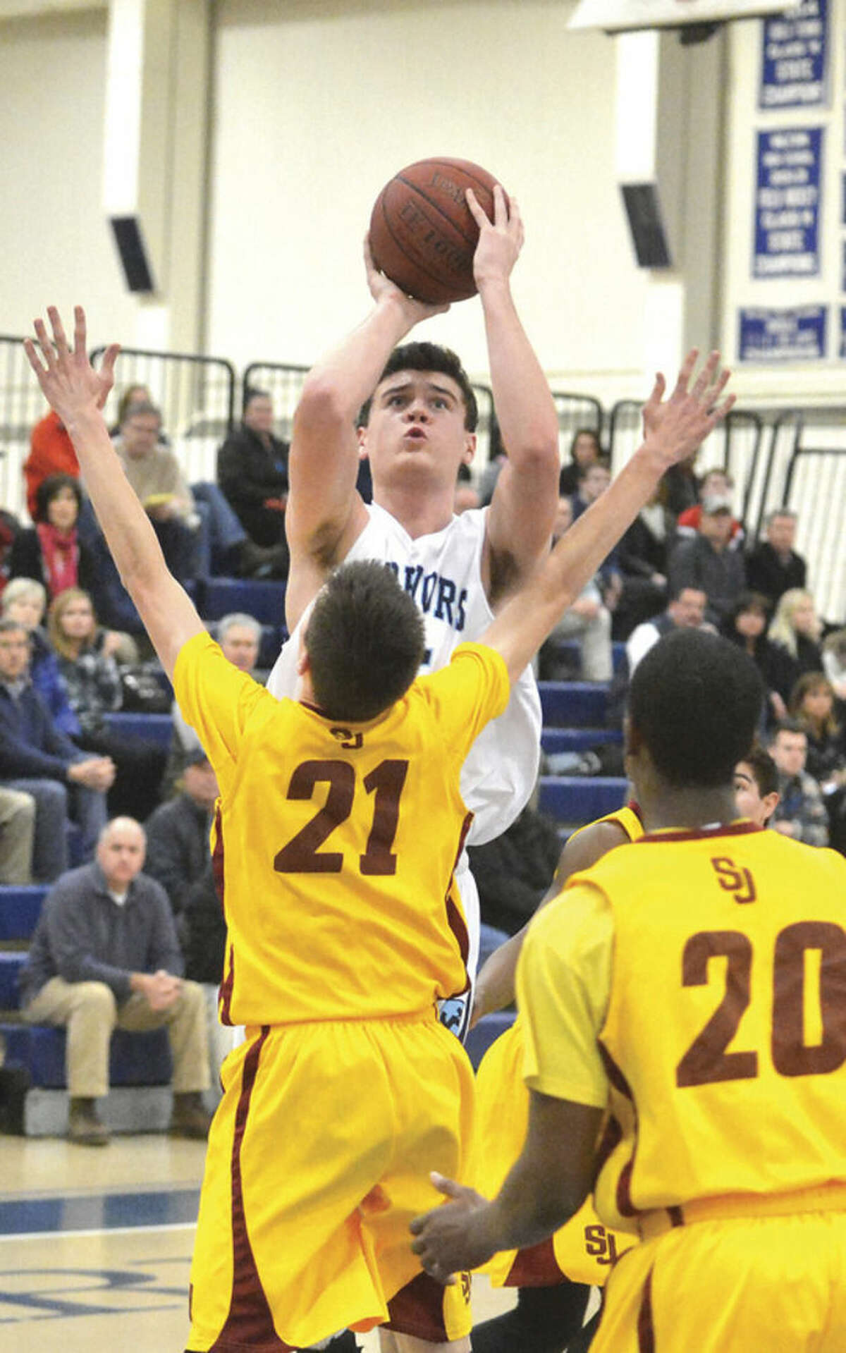Wilton's James Maloney, top, puts up a shot during a game against St. Joseph earlier this season.