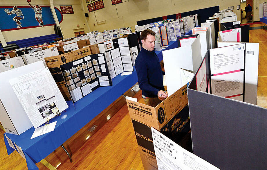 Hour photo / Erik Trautmann Brien McMahon High School biology teacher Joe Laprad looks over entries by his students in the Norwalk Public Schools District-Wide Science Fair at the school Wednesday. More than 400 science projects from students in grade K-12 have were on display since Monday.