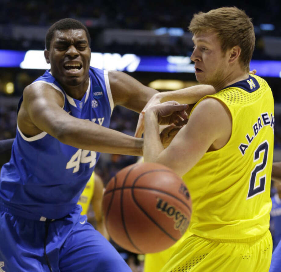 Kentucky's Dakari Johnson (44) and Michigan's Spike Albrecht (2) go after a loose ball during the first half of an NCAA Midwest Regional final college basketball tournament game Sunday, March 30, 2014, in Indianapolis. (AP Photo/Michael Conroy)