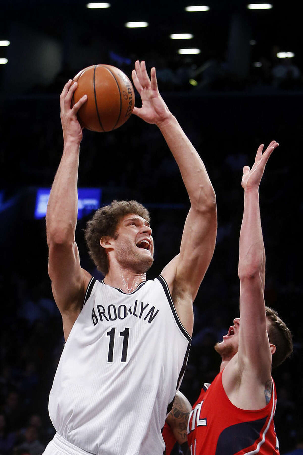 Brooklyn Nets' Brook Lopez (11) goes to the basket against Atlanta Hawks' Mike Muscala during the first half of an NBA basketball game Wednesday, April 8, 2015, in New York. (AP Photo/Jason DeCrow)