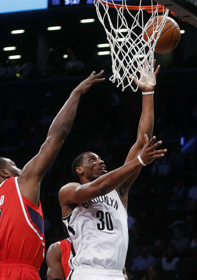 Brooklyn Nets' Thaddeus Young (30) goes to the basket against Atlanta Hawks' Elton Brand, left, during the first quarter of an NBA basketball game Wednesday, April 8, 2015, in New York. (AP Photo/Jason DeCrow)