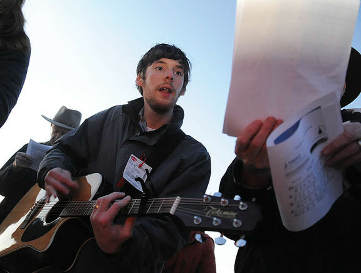 Alex Flydmarshall leads 'The Morning has Broken' on his guitar a the Ecumenical Sunrise Service on Easter Sunday at Compo Beach in Westport. Hour photo/Matthew Vinci