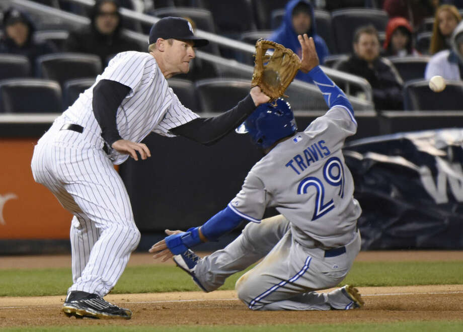 New York Yankees third baseman Chase Headley waits for the ball as Toronto Blue Jays' Devon Travis (29) slides into third base on a single by Blue Jays' Jose Reyes during the fifth inning of a baseball game Wednesday, April 8, 2015, at Yankee Stadium in New York. (AP Photo/Bill Kostroun)