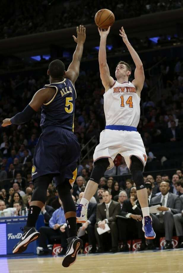 New York Knicks' Jason Smith (14) shoots over Indiana Pacers' Lavoy Allen (5) during the first half of an NBA basketball game Wednesday, April 8, 2015, in New York. (AP Photo/Frank Franklin II)